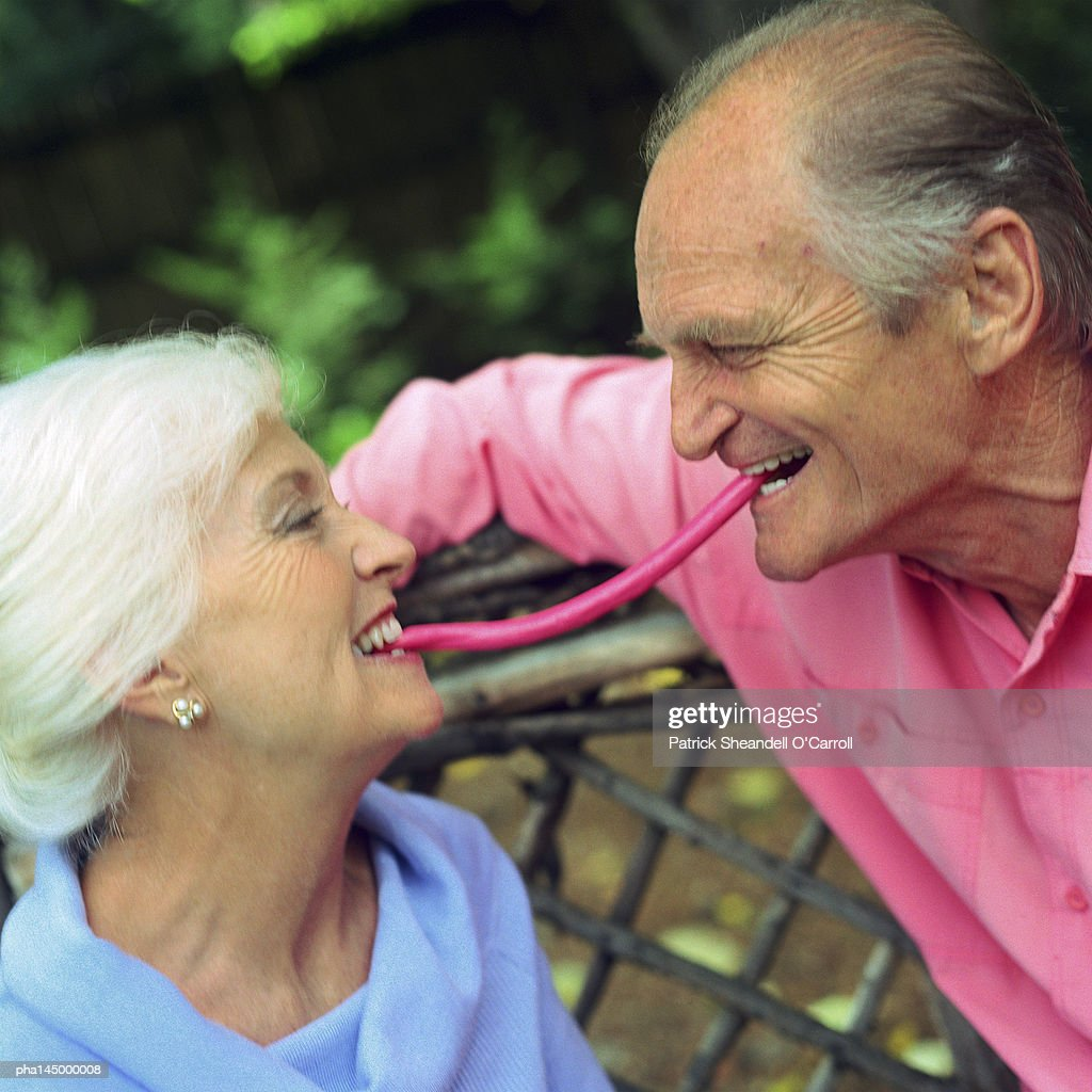 Mature couple face to face, each with one end of piece of candy in mouth between them : Stock-Foto