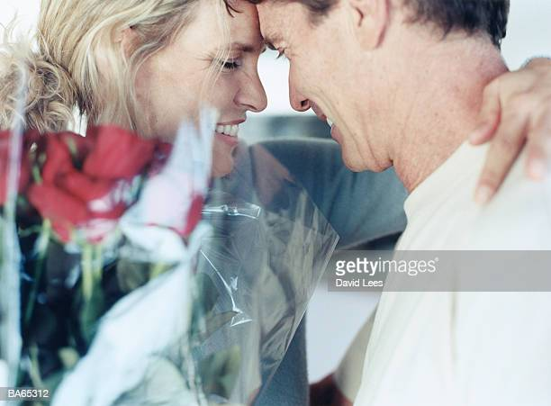 Mature couple face to face, woman holding red roses, close-up