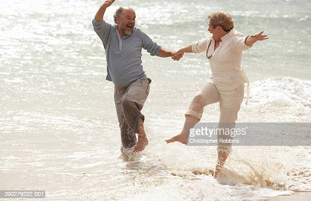 Mature couple hand in hand, splashing in surf, laughing