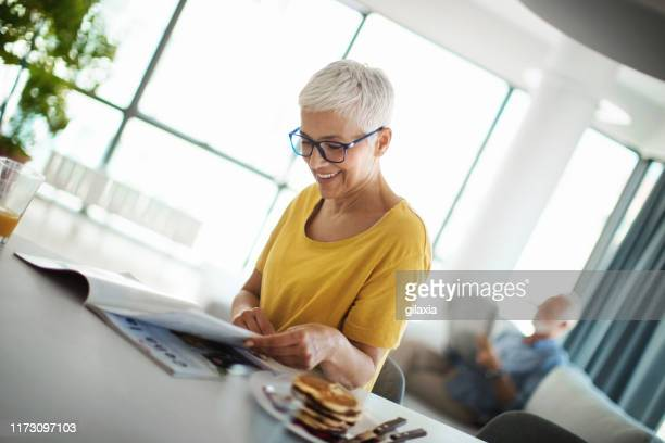 mature couple having a morning coffee at a kitchen counter. - reading stock pictures, royalty-free photos & images