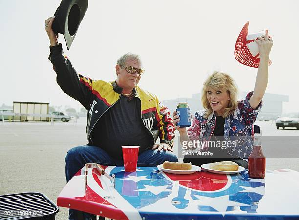 mature couple having  barbeque at parking lot, holding hats - biker jacket stock photos and pictures