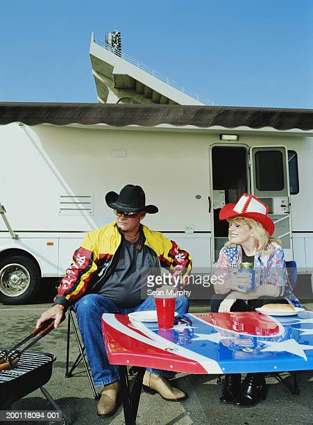mature couple having barbeque outside of trailer - biker jacket stock photos and pictures