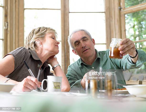Mature couple having breakfast, looking at jar held up by man