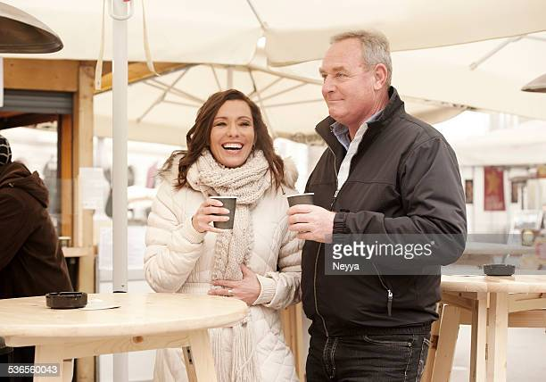 mature couple having coffee outdoors