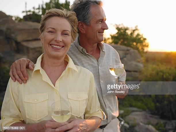 Mature couple having drinks, smiling, sunset