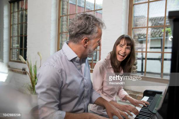 mature couple having fun at home, playing the piano - duet stock pictures, royalty-free photos & images
