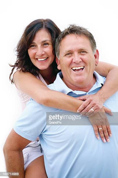 Mature couple having fun giving piggy back ride