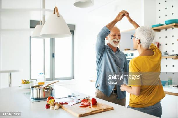 mature couple having fun while cooking lunch. - mature couple stock pictures, royalty-free photos & images