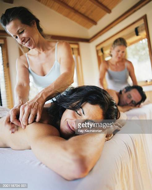 mature couple having massage together in spa - side by side stock pictures, royalty-free photos & images