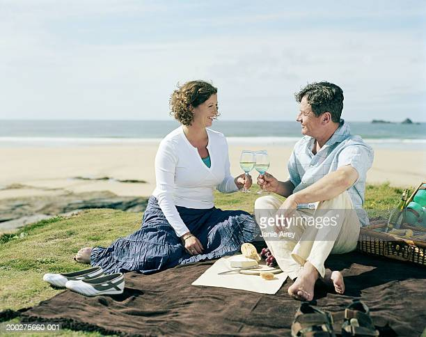 Mature couple having picnic by beach, toasting glasses of wine