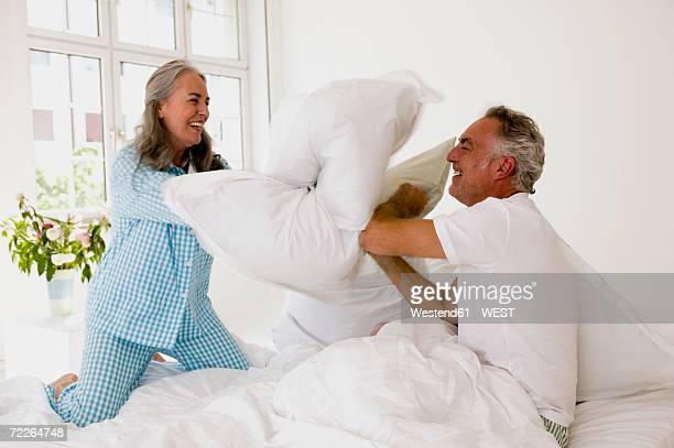 mature couple having pillow fight on bed - nightdress stock pictures, royalty-free photos & images
