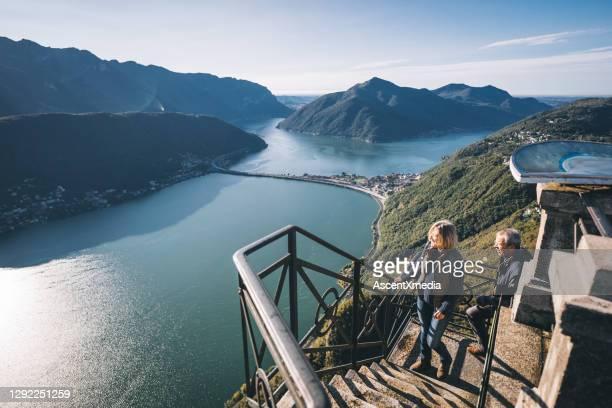 朝の湖ルガーノの上の成熟したカップルのハイキング - スイス ルガーノ ストックフォトと画像