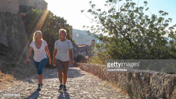 couples mûrs randonnée jusqu'à chemin de pierre à coucher au lever du soleil - mode de vie actif photos et images de collection