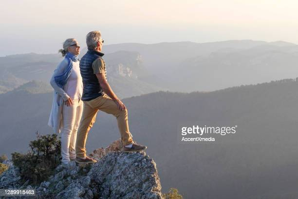 mature couple hikes along sunny mountain ridge in the morning - early retirement stock pictures, royalty-free photos & images