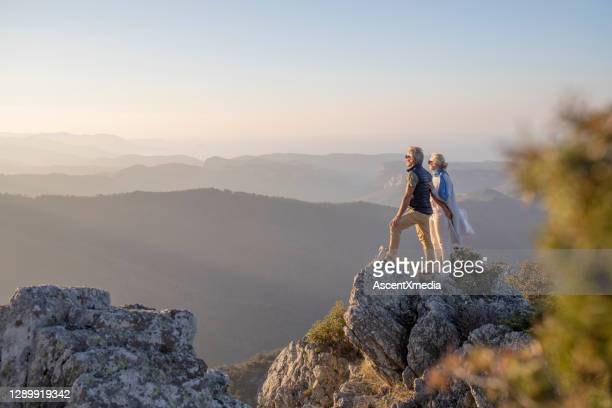 mature couple hikes along sunny mountain ridge in the morning - focus on background stock pictures, royalty-free photos & images
