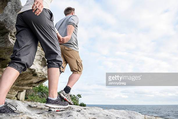 Mature couple hiking on rocks holding hands, Bondi Beach