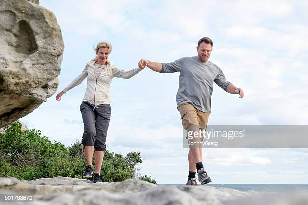 Mature couple hiking on rocks holding hands, Bondi Beach