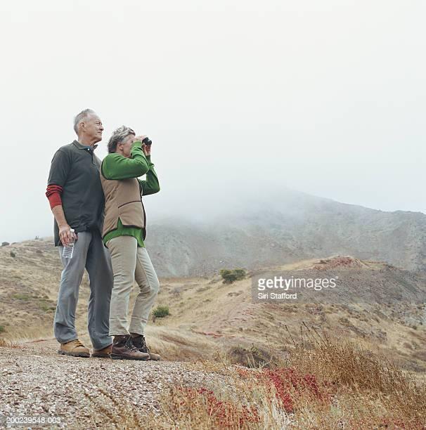 Mature couple hiking, woman with binoculars