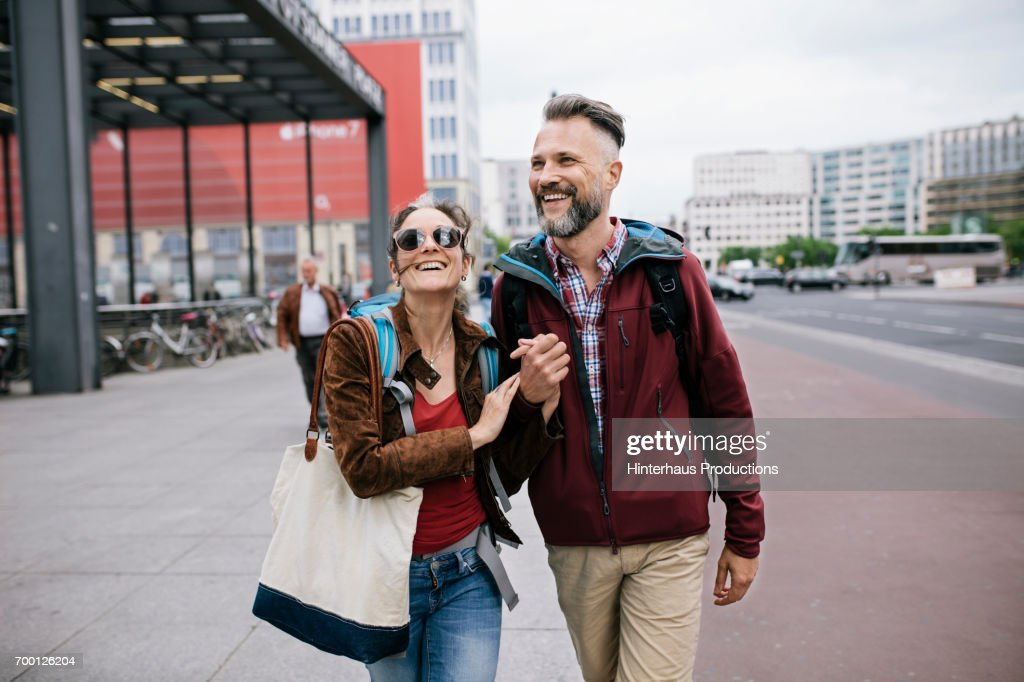 A Mature Couple Hold Hands As They Walk Through Berlin : Stock Photo