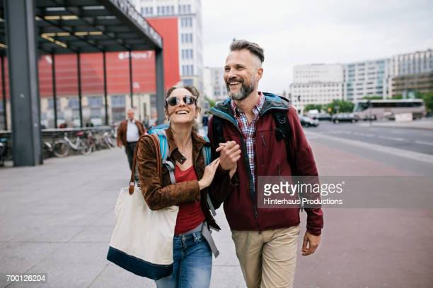 a mature couple hold hands as they walk through berlin - tourist stock-fotos und bilder