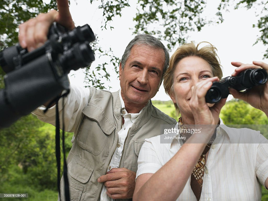 Mature couple holding binoculars, man pointing ahead, smiling : Stock Photo