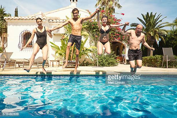 Mature couple holding hands with son and daughter jumping into in swimming pool