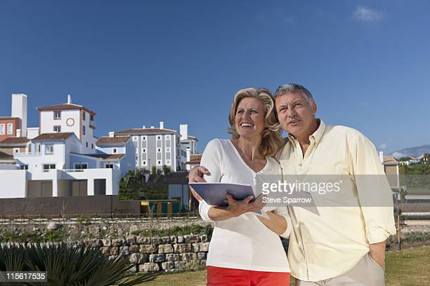 Mature couple holding realestate booklet