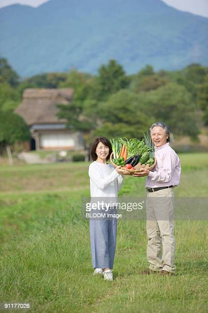 Mature couple holding vegetables in basket in countryside, portrait