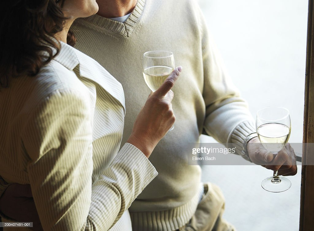 Mature couple holding wine glasses, mid section : Stock Photo