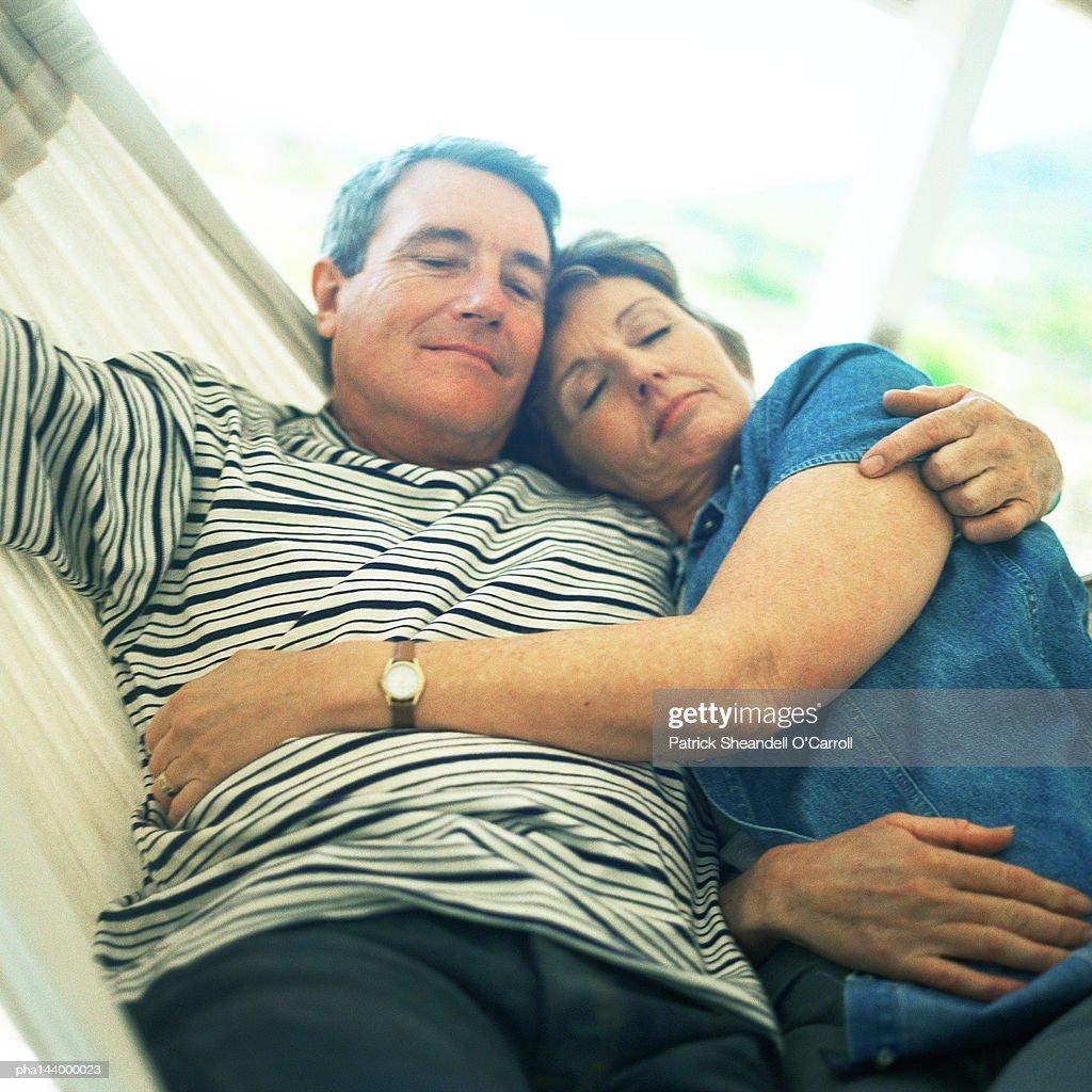 Mature couple hugging in hammock : Stockfoto
