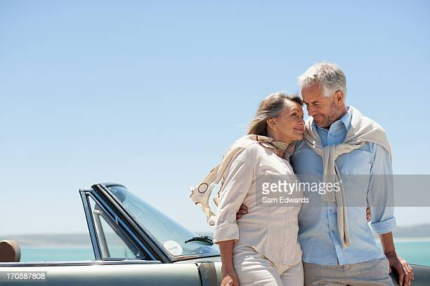 Mature couple hugging next to convertible