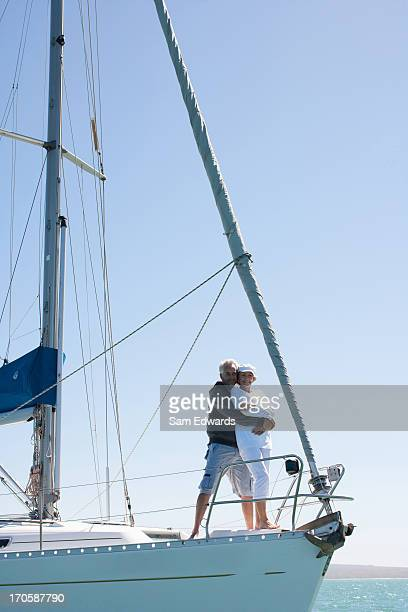 mature couple hugging on deck of sailboat - yachting stock pictures, royalty-free photos & images