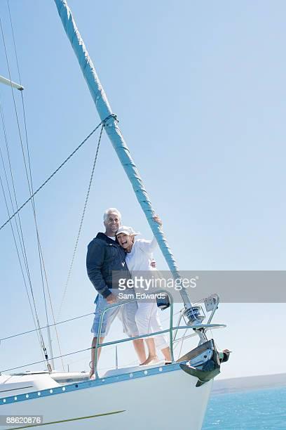 couple d'âge mûr embrassant sur le pont du bateau à voile