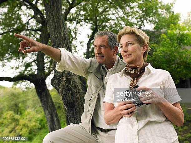 Mature couple in African bush, woman holding binoculars, man pointing