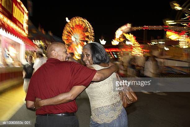 Mature couple in amusement park, woman looking over shoulder at camera, night
