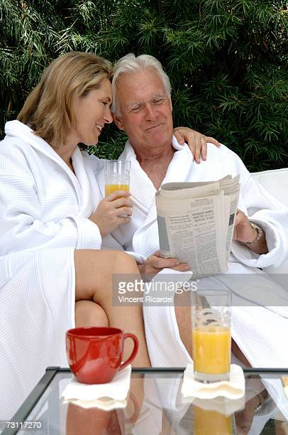 Mature couple in bathrobes reading paper on porch