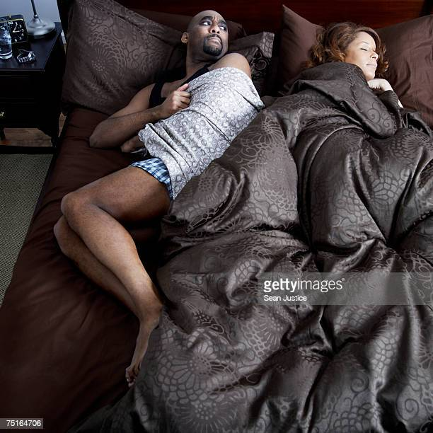 Mature couple in bed, man trying to steal covers from woman, elevated view