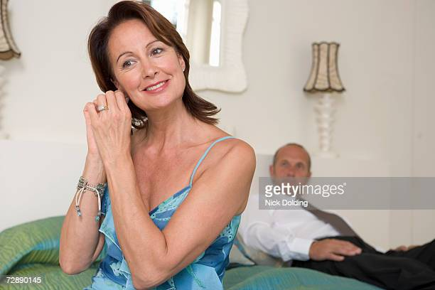Mature couple in bedroom, woman putting on earrings