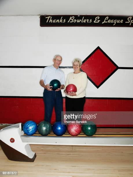 mature couple in bowling alley holding balls - ボーリング場 ストックフォトと画像