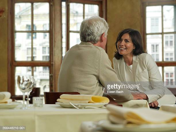 Mature couple in cafe, holding hands over table, woman smiling