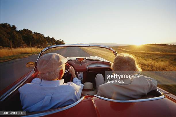 mature couple in car, rear view - convertible stock pictures, royalty-free photos & images