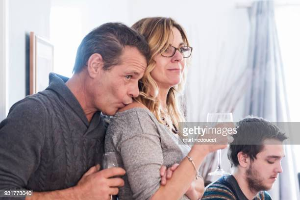 Mature couple in family reunion watching video hommage.