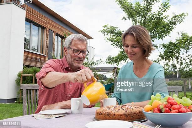 Mature couple in garden having afternoon break