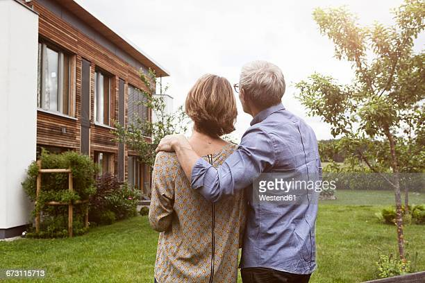 Mature couple in garden looking at house