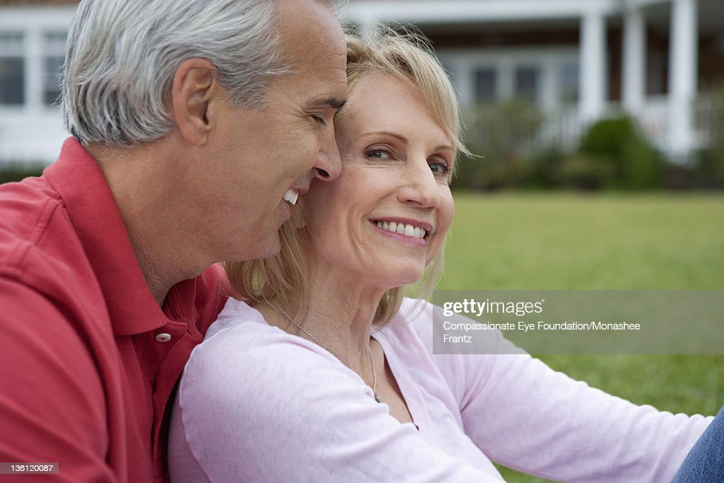 Mature couple in garden, smiling : Stock Photo