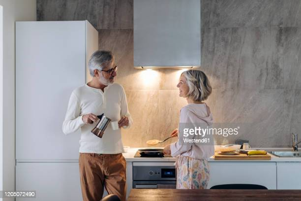 mature couple in kitchen at home in the morning - 妻 ストックフォトと画像