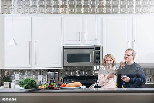 Mature couple in kitchen drinking red wine