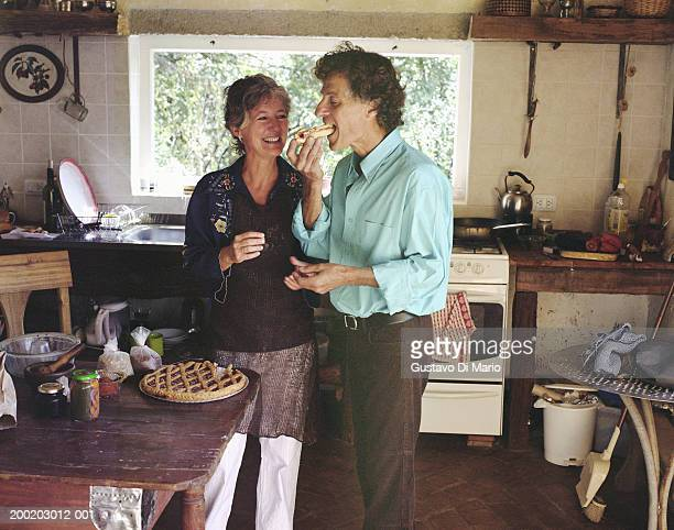 Mature couple in kitchen, man eating wedge of pie
