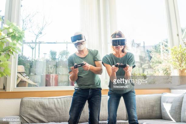 Mature couple in kiving room at home wearing VR glasses playing video game