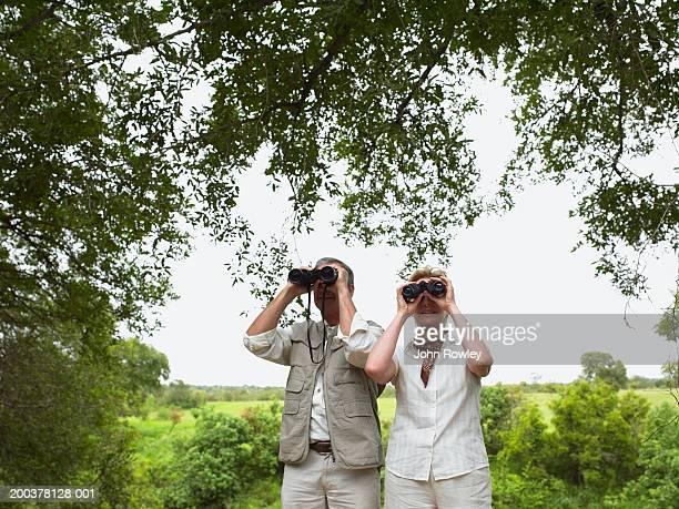 Mature couple in landscape using binoculars